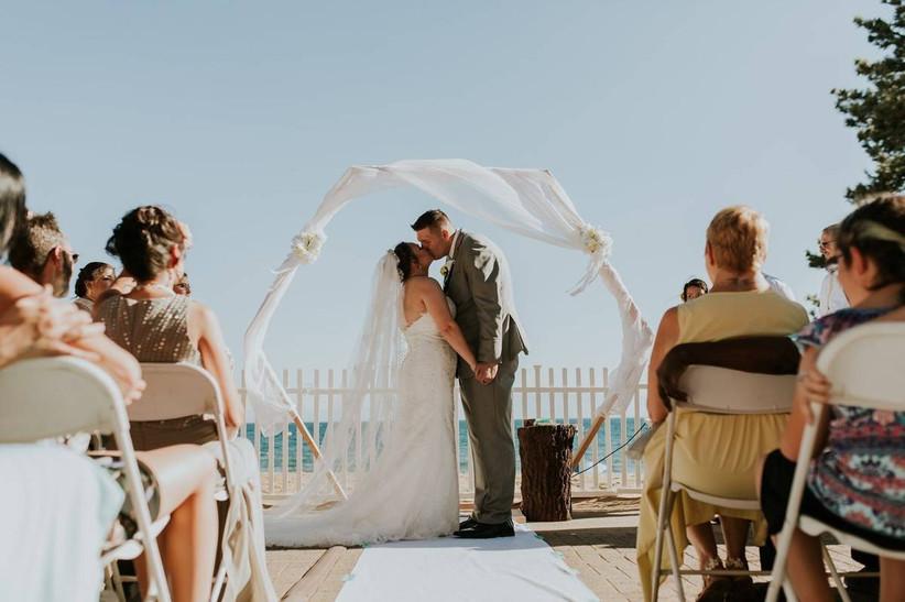 newlywed couple kissing at wedding ceremony