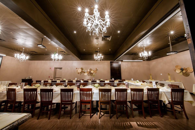 elegant banquet room with dark wood accents and two long reception tables