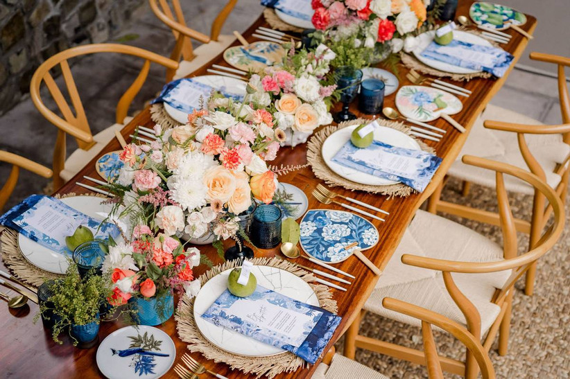 boho wedding tablescape with blue floral print paper fans, rattan place mats, and bright pink and orange centerpieces