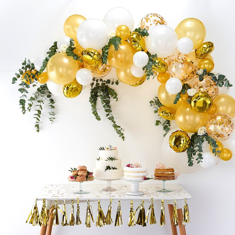 Fun, decorative balloon arch with greenery over dessert table