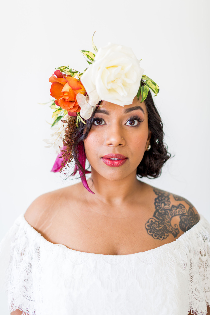 Bride looking directly at camera with asymmetrical flower crown made from roses, greenery and lunaria