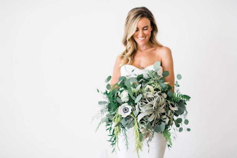 bride stands against white wall holding beach wedding bouquet of greenery eucalyptus anemones and air plants