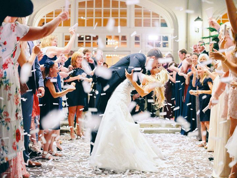 Romantic shot of couple kissing as guests throw confetti