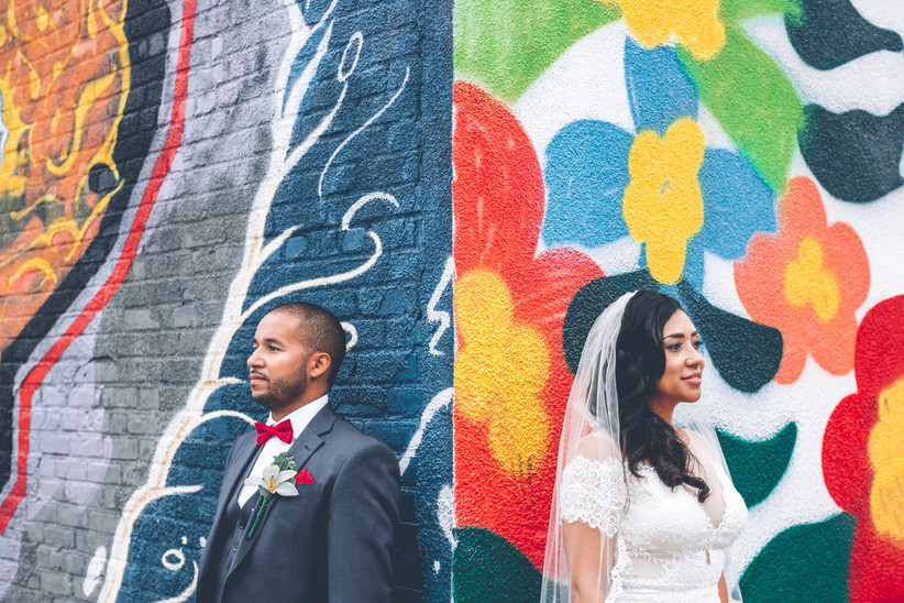Black couple stands in front of outdoor flower mural painted with bright wedding colors orange red yellow blue