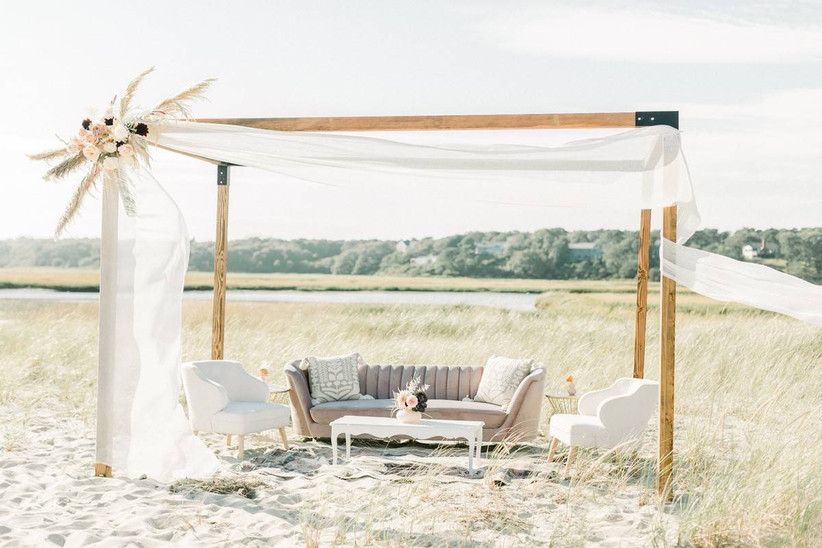 upholstered chairs and sofa sit beneath an outdoor wooden cabana draped with white fabric. there is a water view in the distance