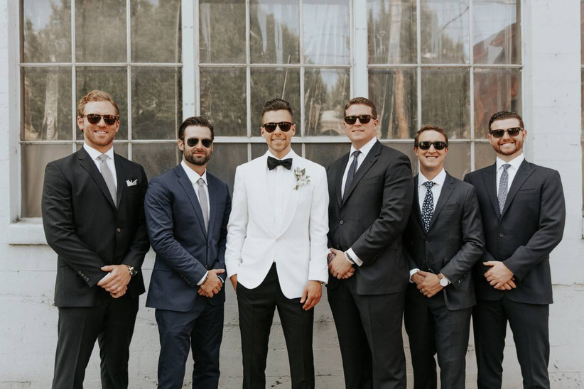 groom and groomsmen pose for a wedding portrait while wearing sunglasses