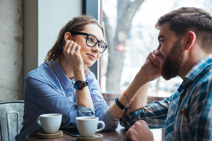 woman and man sitting in a coffee shop looking at each other romantically