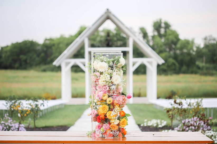 clear acrylic rectangular tower filled with loose pink, yellow, and white flowers