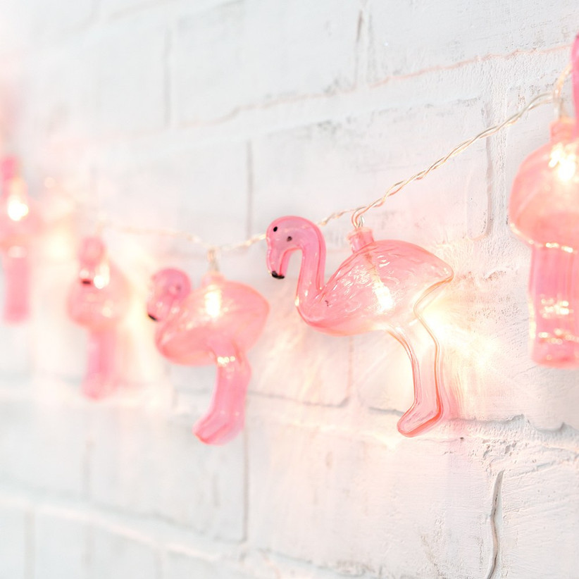 Flamingo string lights strung against white brick wall