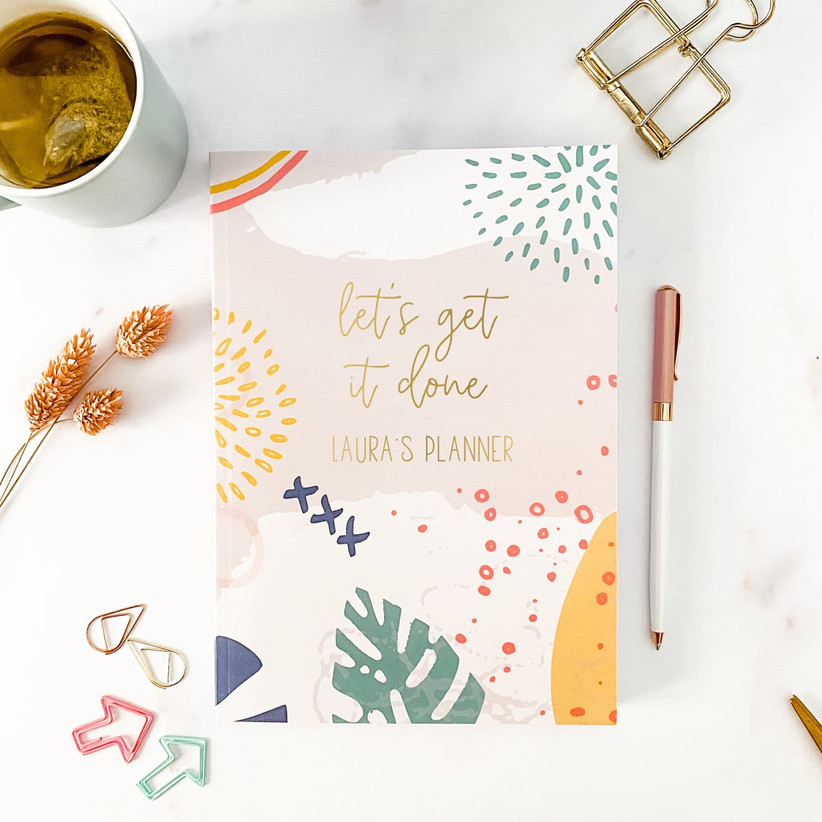 Colorful custom planner with Let's Get It Done and Laura's Planner on the front in gold