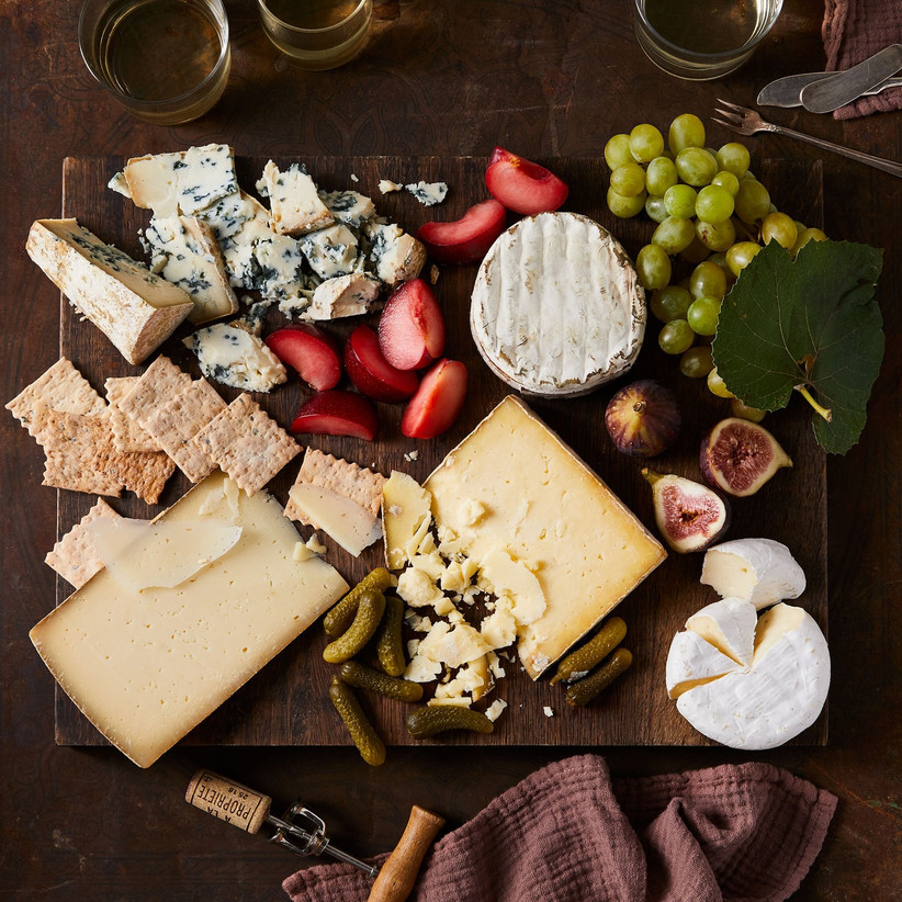 Decadent cheese board with fruit and pickles