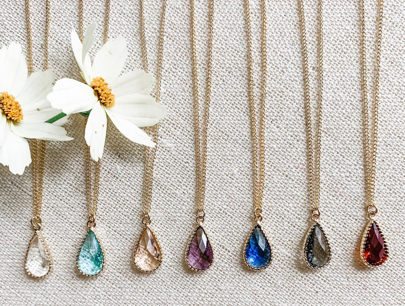 Seven teardrop gemstone bridesmaid necklaces with different color crystals on a gold chain