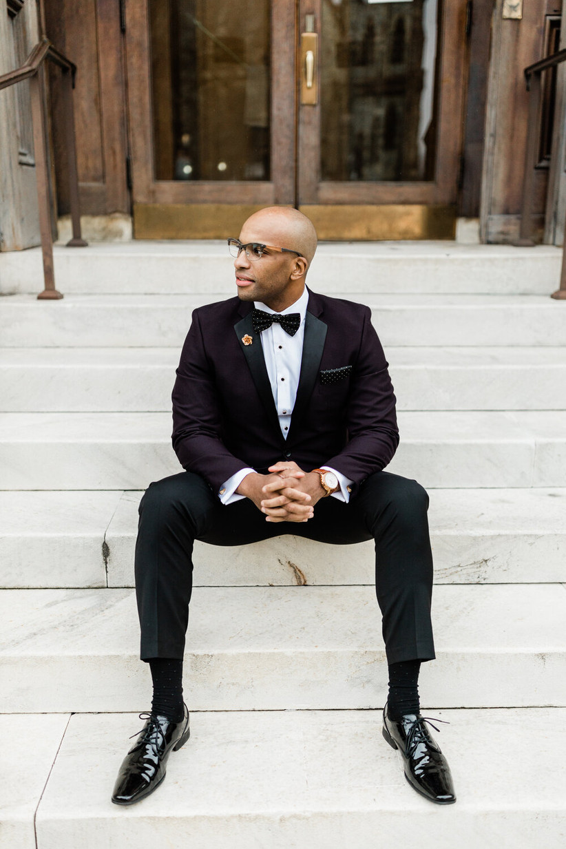 groom sitting on a staircase outdoors wearing winter wedding colors dark plum tuxedo jacket with black dress pants and patent leather shoes