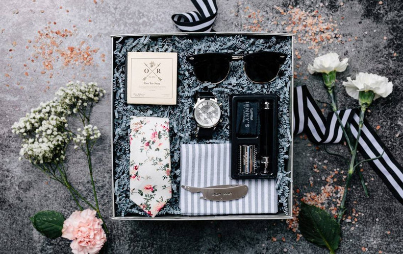 Groomsmen gift box with sunglasses, a watch, a floral tie, and other gifts