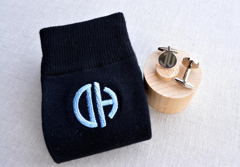 Black socks with white monogram next to yellow-toned metal wedding cuff links with matching monogram