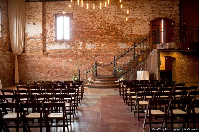 wedding ceremony in industrial space with brick walls and staircase