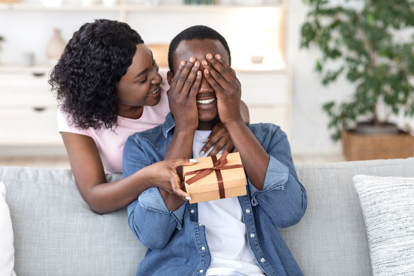 Boyfriend sitting on sofa covering eyes with eyes as girlfriend presents a gift from behind him