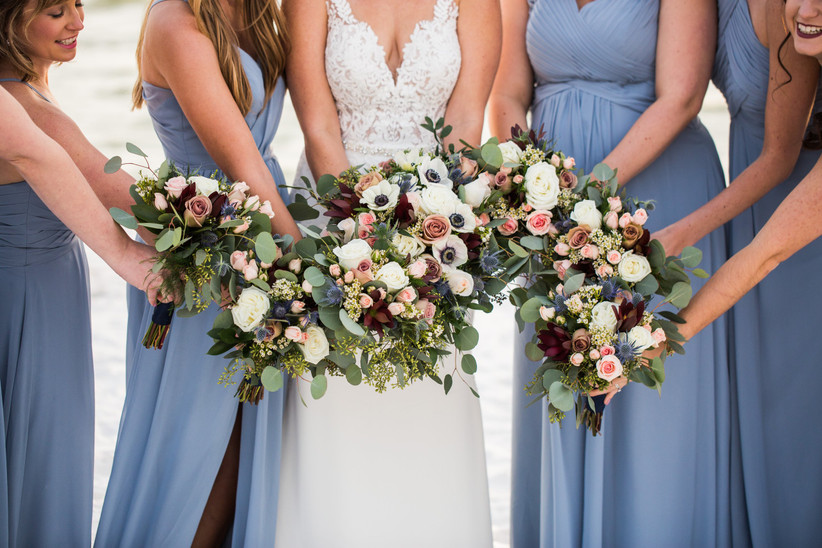 Bride and bridesmaids pose in a circle while holding their wedding bouquets in the center