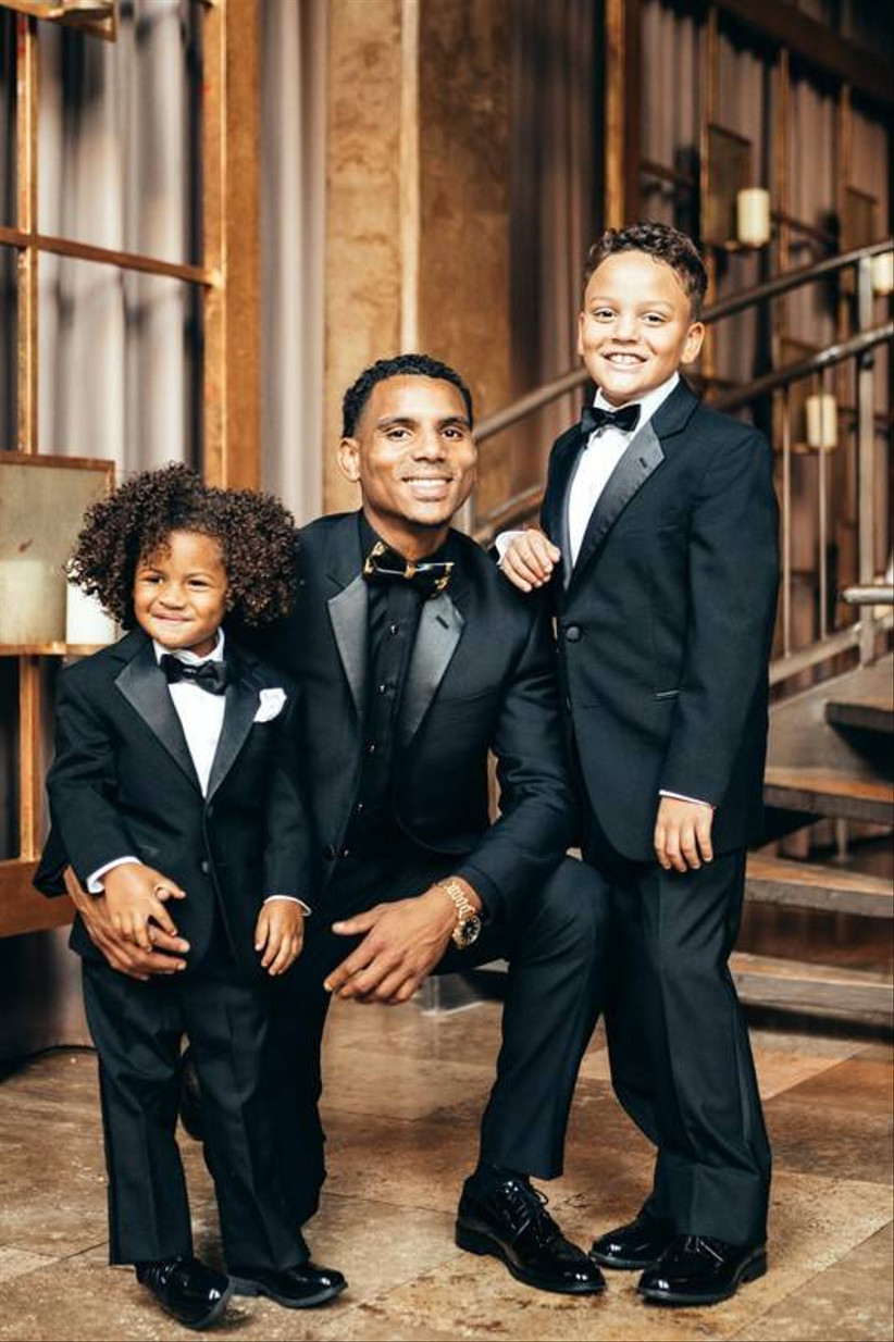 groom flanked by two ring bearers all wearing tuxedos