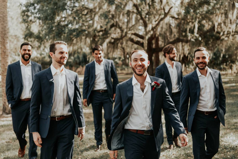 groom smiles at the camera while walking through the grass with his groomsmen