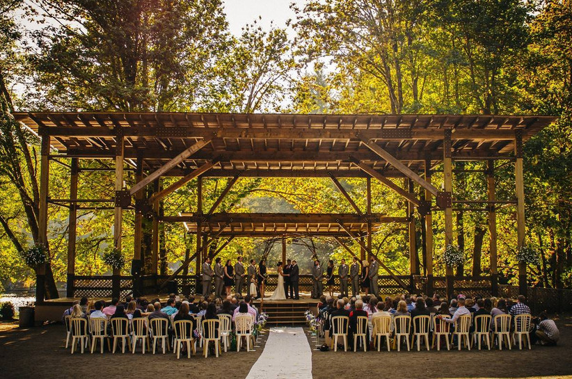 outdoor wedding venue in oregon beneath large wooden pergola surrounded by trees
