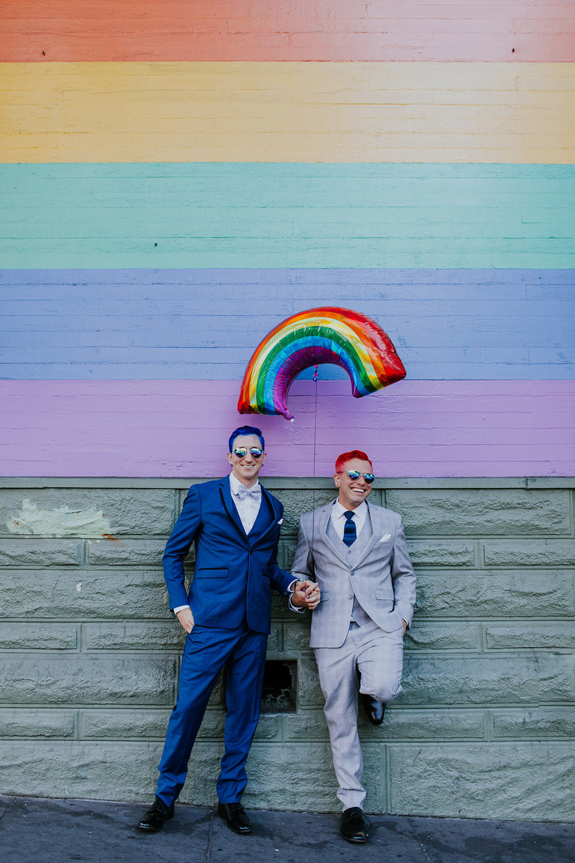 same-sex couple holding hands standing with backs agains a wall and a rainbow balloon above them