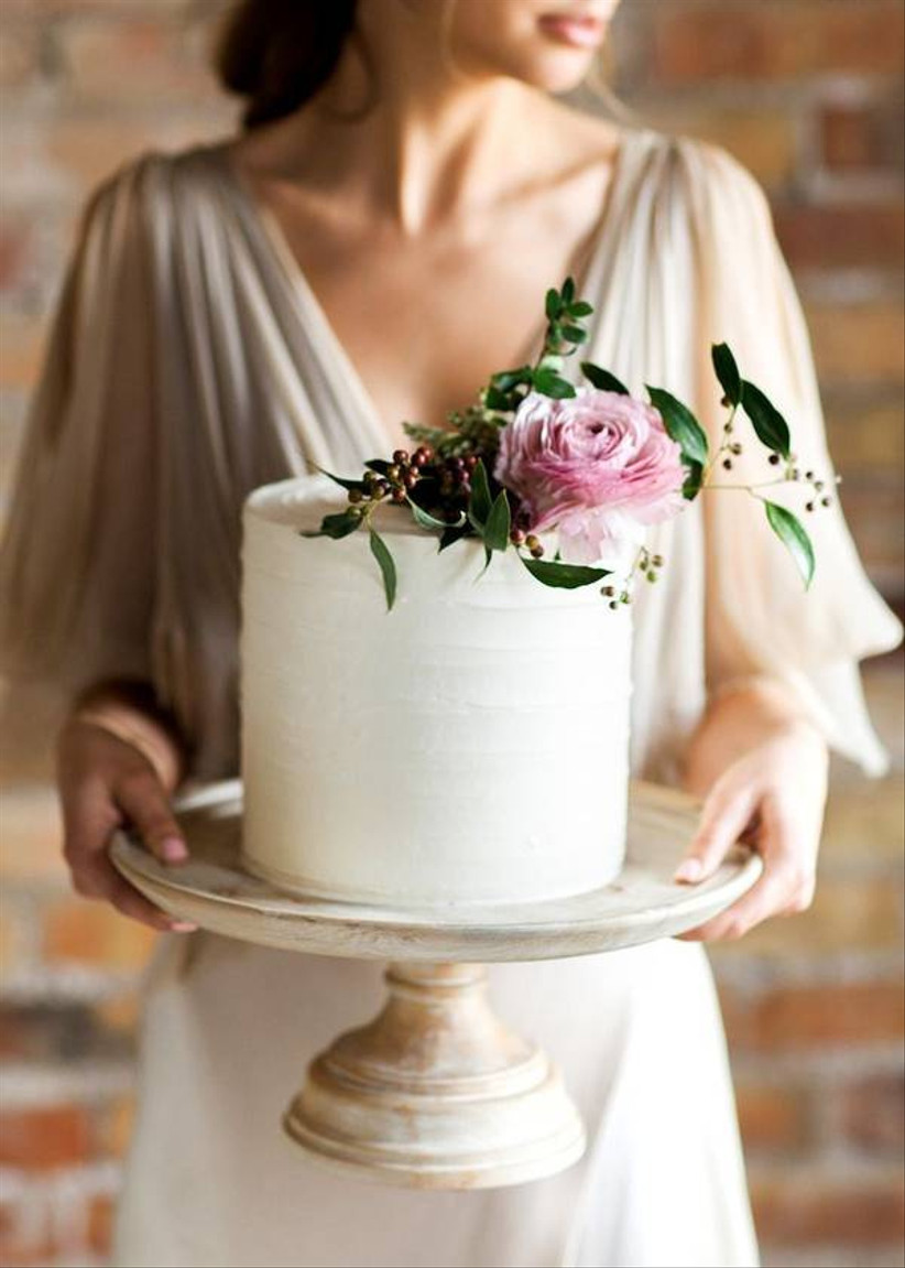 bride holds small wedding cake with one pink flower on top