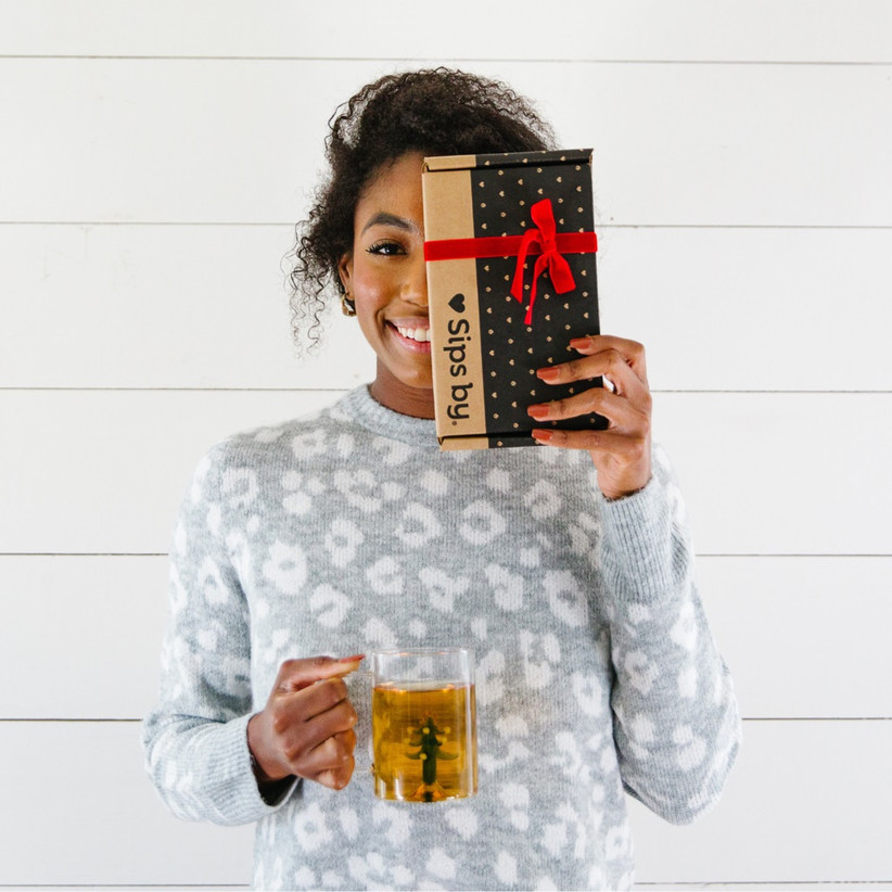 Women holding Sipsby subscription box in one hand and cup of tea in the other