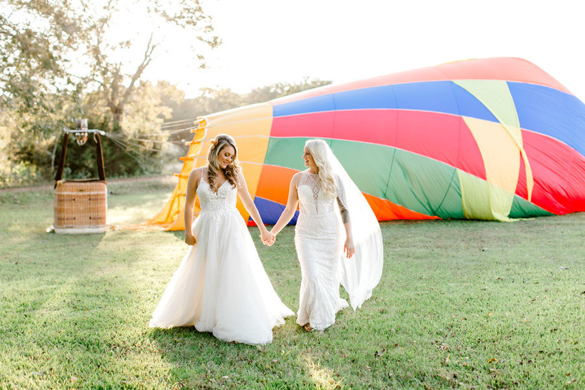 two brides hold hands as they walk in front of a hot air balloon on the grass