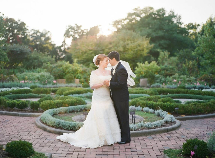 bride and groom pose foreheads touching holding hands looking into each other's eyes at dusk while standing in formal garden