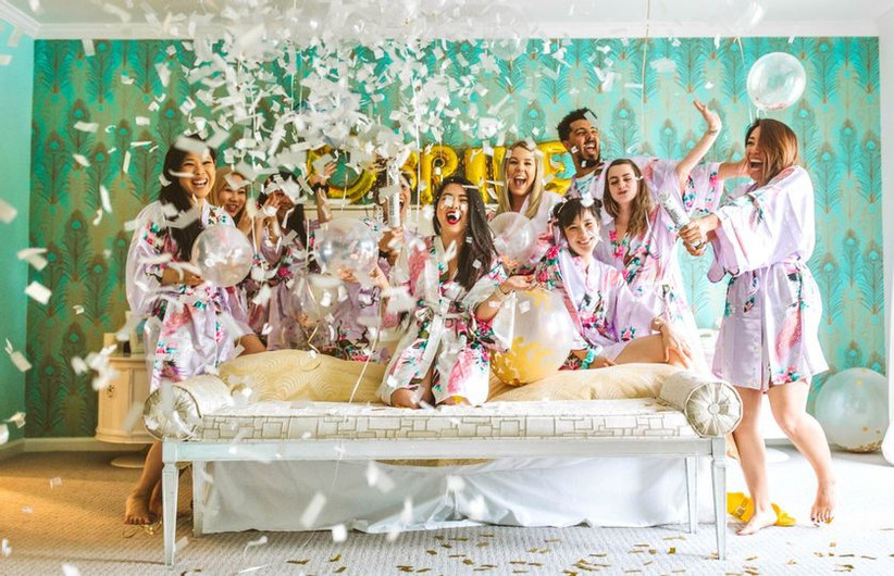 Bride and her bridal party celebrating in a hotel room decorated with balloons and confetti