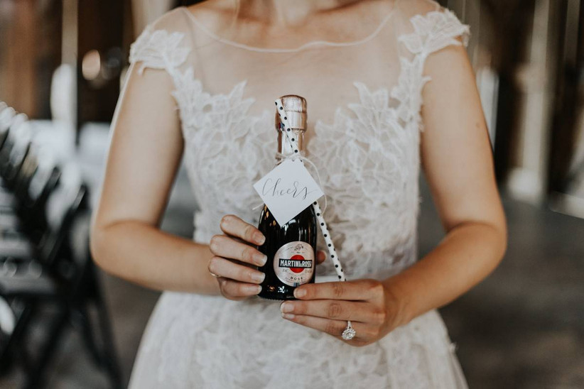 bride holds miniature bottle of rose with polka dot paper straw