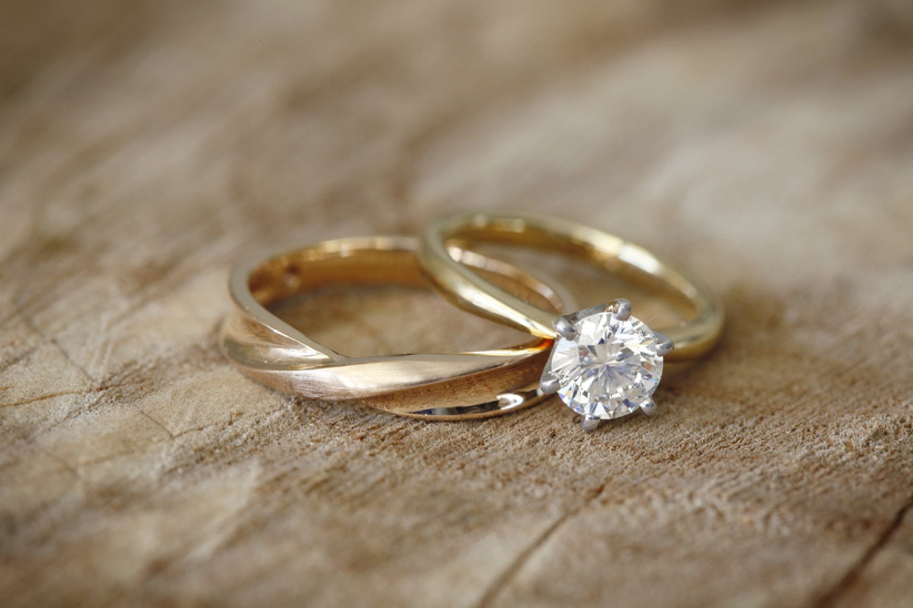Solitaire engagement ring with plain gold band next to gold wedding band