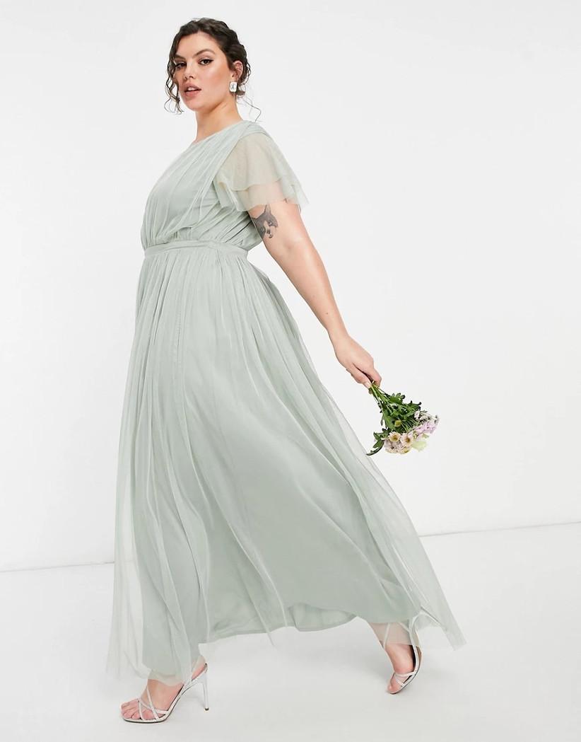 Model wearing sage green chiffon bridesmaid dress with sheer ruffled sleeves