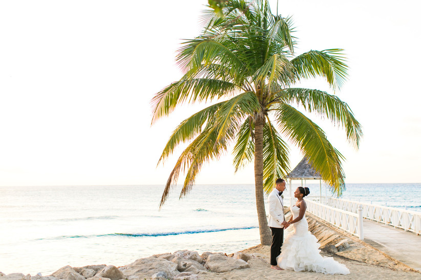 black couple stands on the beach under a palm tree with pier and gazebo in the background