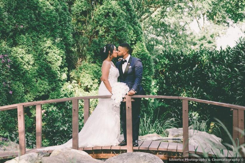 bride and groom kissing on bridge in garden
