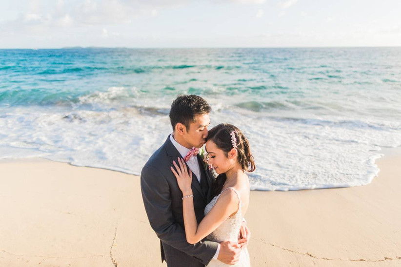 groom and bride kissing near the ocean