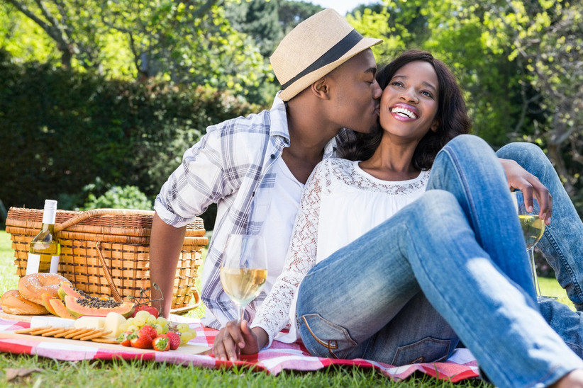 Man kissing woman on the cheek sitting on picnic blanket in sunlight