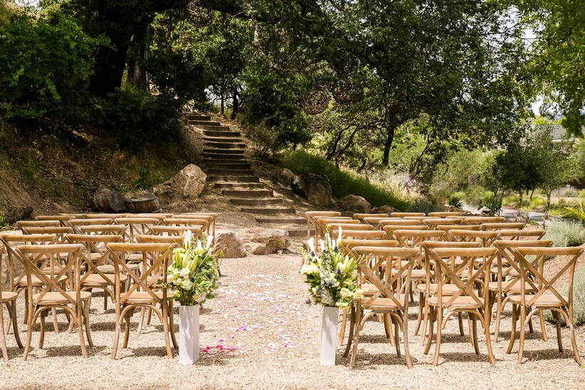 outdoor wedding ceremony at napa venue empty wooden chairs set in rows surrounded by lush green trees