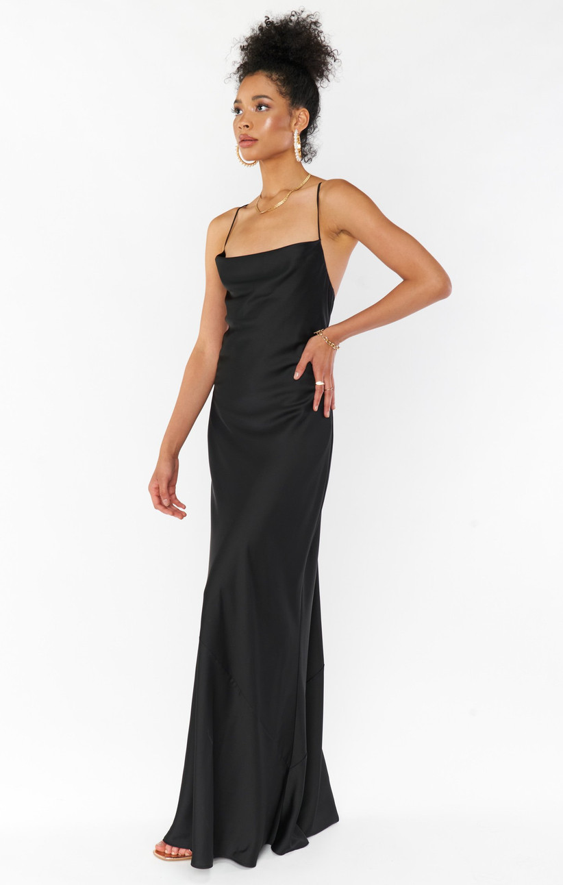 Black model stands with her hand on her hip while looking off to the side and wearing black floor-length bridesmaid dress trend with cowl neckline