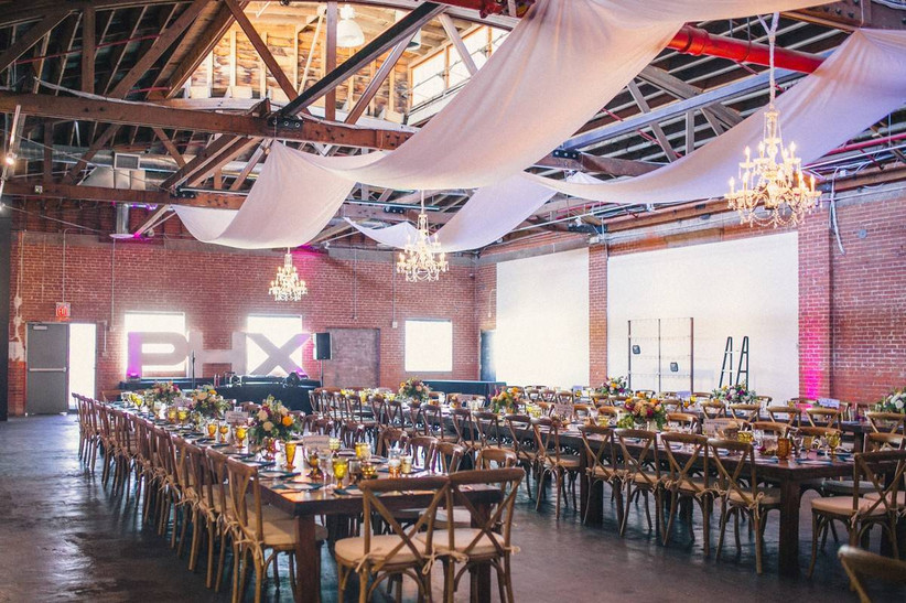 modern indoor wedding reception with brick walls and white draped ceilings