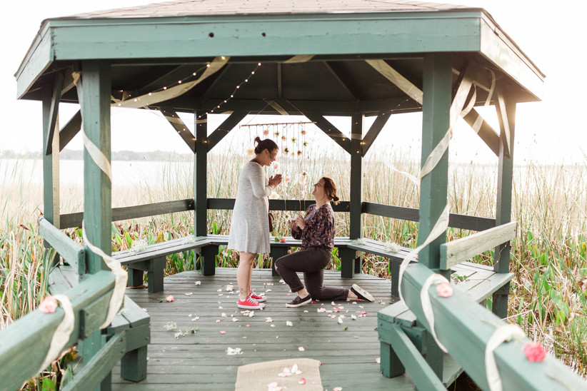 proposal at waterfront gazebo decorated with flower petals