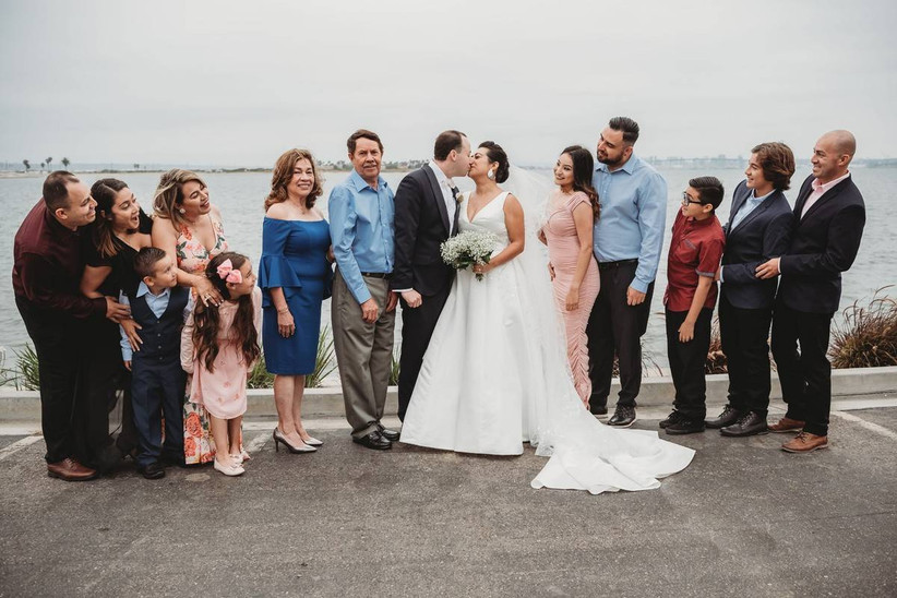 wedding couple kissing surrounded by happy family members