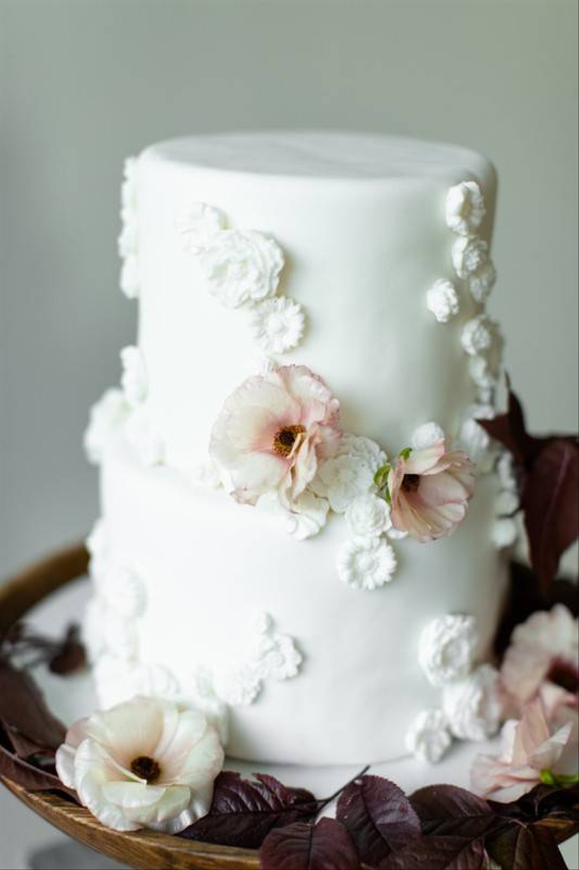 close-up of a wedding cake decorated with delicate pink flowers