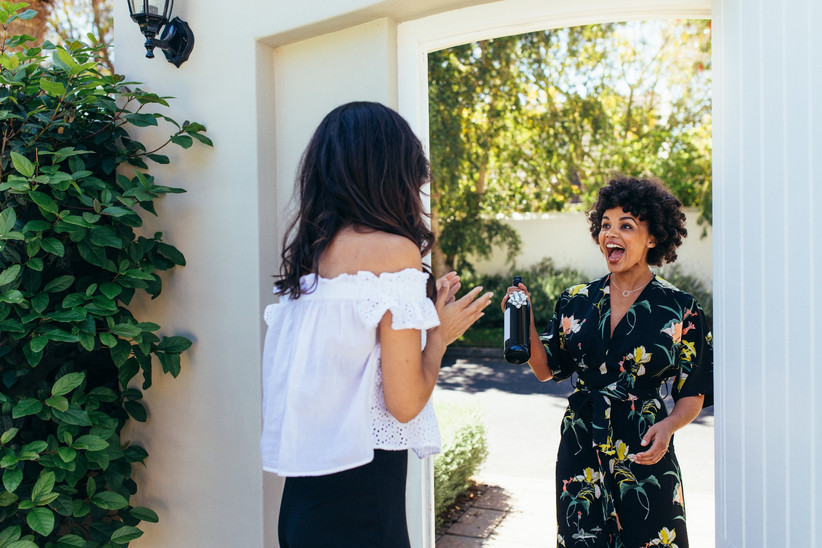Woman greeting smiling friend at the door who has bottle of wine in hand