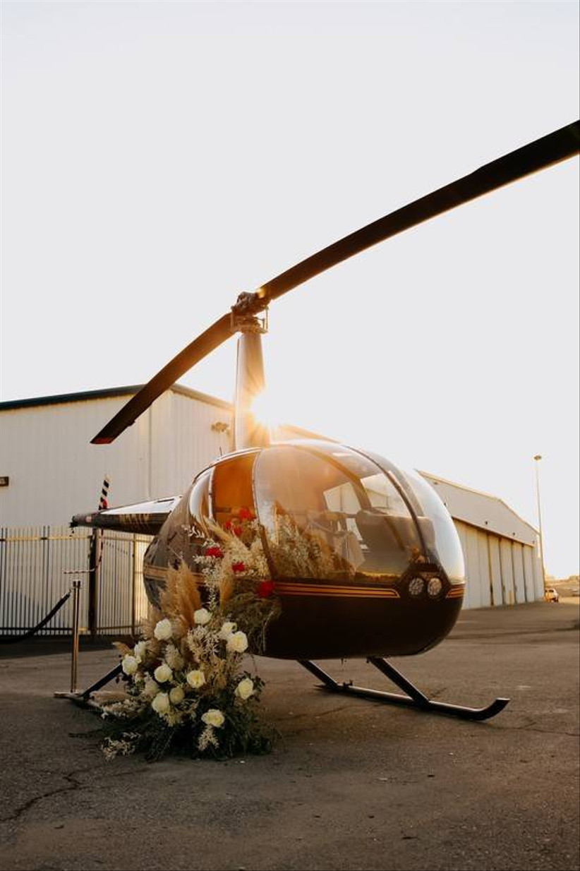 helicopter parked on asphalt decorated with boho flower arrangement
