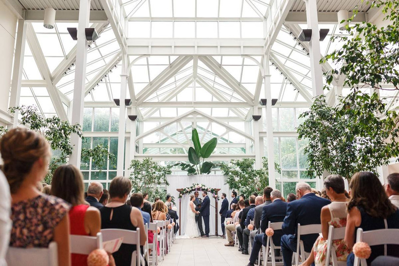 indoor wedding ceremony botanical conservatory with tall ceilings glass ceilings letting in a lot of light