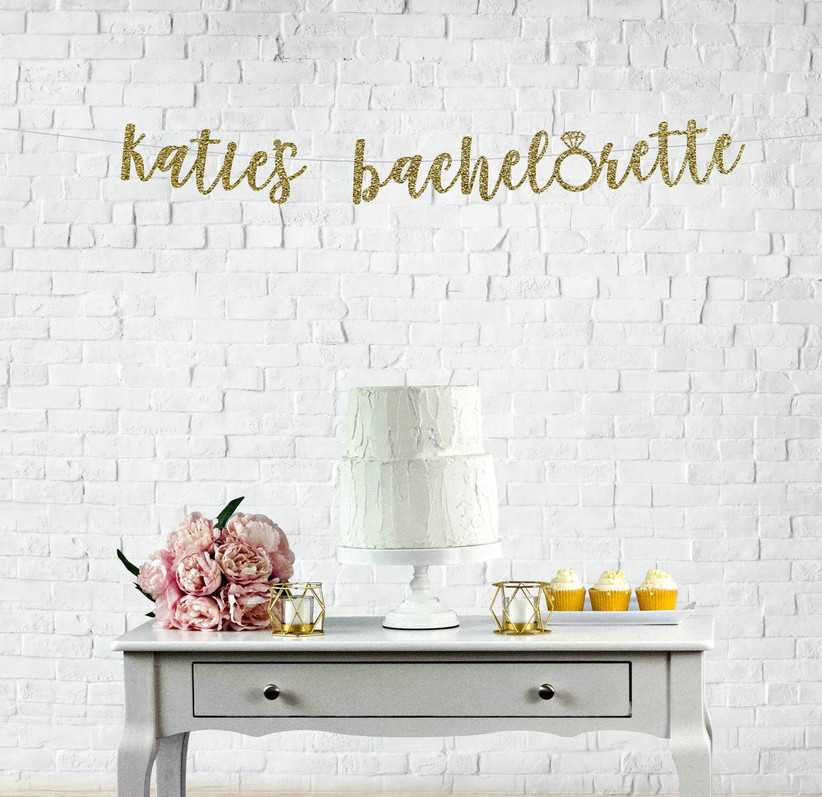 Personalized glittery gold bachelorette banner reading Katie's Bachelorette displayed over a vintage cake table