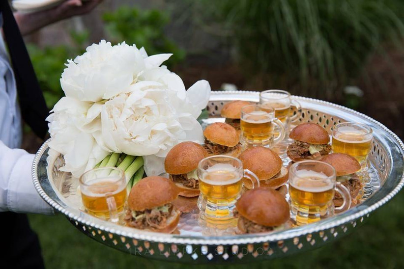 sliders and mini glasses of beer on a silver catering platter