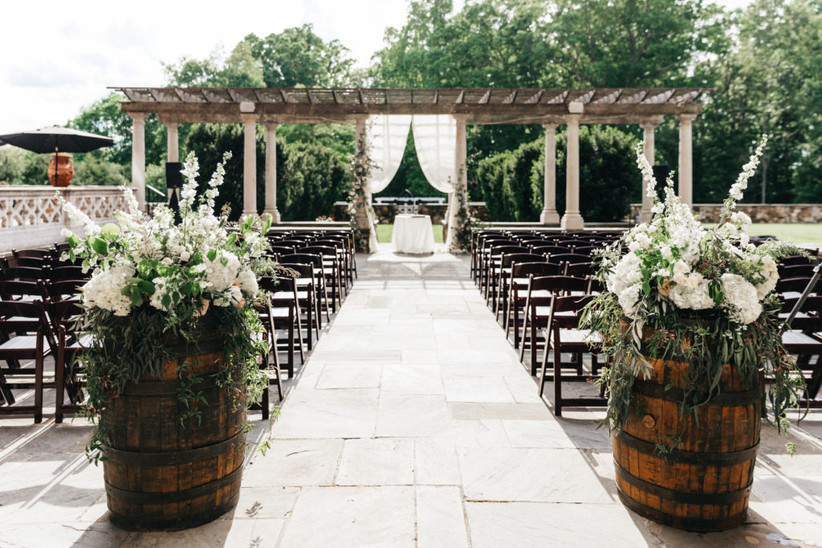 wedding prelude songs - outdoor wedding ceremony venue looking toward the altar from the back of the aisle. two wine barrels are placed on either side of the aisle and decorated with fresh flowers on top